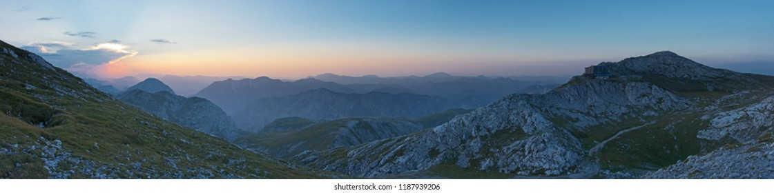 Panoramic view from Hochschwab over surrounding mountains in Styria under clear dusky blue sky at sunset in summer.