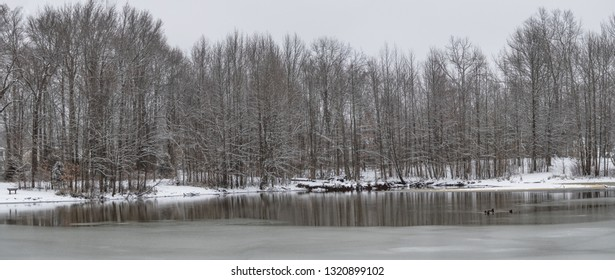 A panoramic view of Holiday Lake with ice and fresh snow in Manalapan New Jersey.