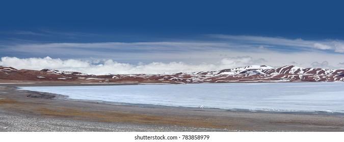 Panoramic view of holy Rakshas Tal lake under ice in Ngari, Western Tibet, China. This lake also known as Demons Lake, Ravana Tal or Ravan Harda in Hindu Religion.