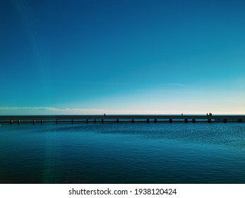 panoramic view of the horizon with a bridge over the sea and a big blue sky