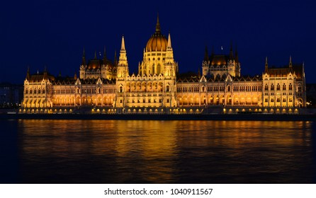 Panoramic view of Hungarian Parliament reflecting in Danube river. Night cityscape of Budapest