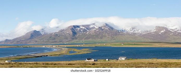 Panoramic View of Idyllic Icelandic Landscape with Snow Covered Mountains, Blue Sky and Water