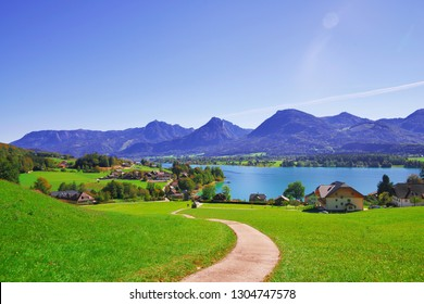 Panoramic view of idyllic mountain scenery in Alps with fresh green meadows in bloom on a beautiful sunny day in springtime, Wolfgangsee lake in Austria, Salzkammergut, small tourist town St. Wolfgang