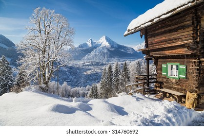 Panoramic view of idyllic winter mountain scenery with traditional mountain chalet in the Alps on a sunny day with blue sky