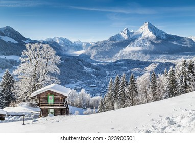 Panoramic view of idyllic winter wonderland mountain scenery with traditional mountain chalet in the Alps on a sunny day with blue sky