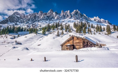 Panoramic view of idyllic winter wonderland with mountain tops and traditional mountain chalet in the Alps on a sunny day with blue sky, Muhlbach am Hochkonig skiing resort, Salzburger Land, Austria