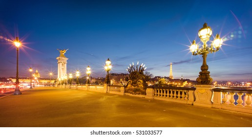 Panoramic view of the illuminated the Alexander III Bridge at dusk. It's a deck arch bridge, regarded as the most ornate, extravagant bridge in the city.