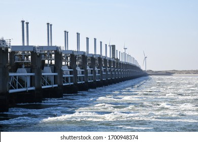 Panoramic view of the inlet of the Oosterschelde storm surge barrier in the province of Zeeland in the Netherlands with water rushing through; windmills in the background