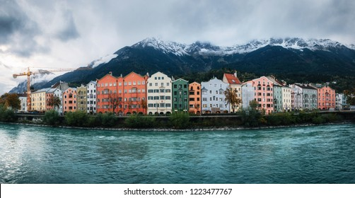Panoramic view of Innsbruck with colorful houses along Inn river and famous Austrian snowy mountains in the background, Tyrol, Austria