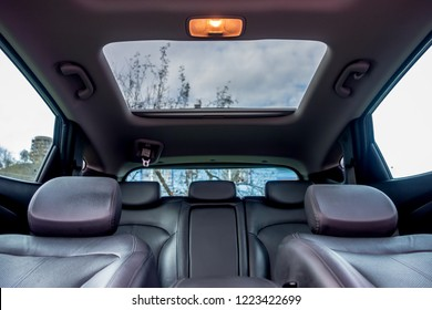 Panoramic view inside car - double sunroof hatch with tinted glass. Sliding panoramic sunroof and luxurious leather seats. Close up photo with bright blue sky seen through sunroof.