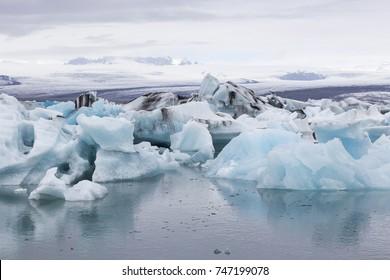 Panoramic view of Jokulsarlon Glacier Lagoon's turquoise and black icebergs in grey weather, Iceland