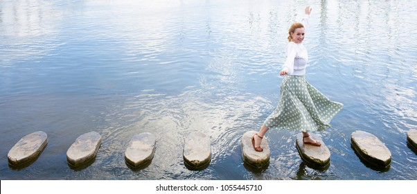 Panoramic view of joyful young woman playful stepping on stone steps crossing water in coastal destination on holiday, sunny outdoors. Fun female looking, travel recreation adventure leisure lifestyle