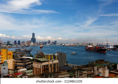 A panoramic view of Kaohsiung Harbor with ships & ferry boats navigating & parking in the seaport & landmark 85 Sky Tower standing among modern buildings under blue sky on a sunny summer day in Taiwan