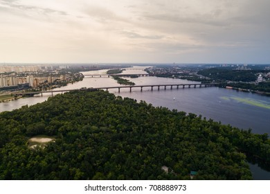 Panoramic view of Kiev city with the Dnieper River in the middle. Aerial view of the residential district and industrial Zone at sunset. Two banks of the river connected by bridges