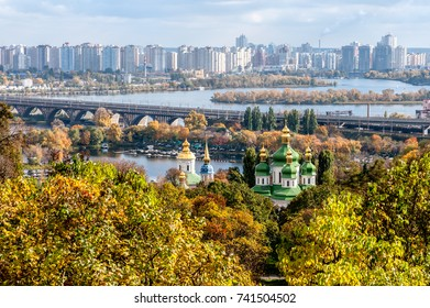 Panoramic view of Kiev city and George Cathedral of the Vydubychi Monastery among the trees of the park in autumn. Kiev, Ukraine.