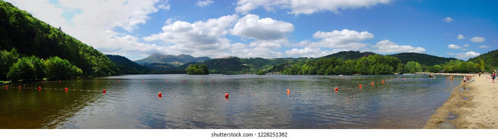 panoramic view of Lake Aydat and the beach in Auvergne, Puy de Dome. With chain of volcanoes in the background