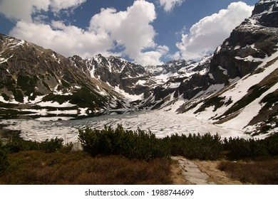 Panoramic view of lake of Czarny Staw Gasienicowy covered with snow. Surrounding peaks of Tatra Mountains in Zakopane, Poland - Shutterstock ID 1988744699
