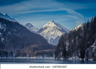 Panoramic view of a lake in the European Alps, dark, cloudy background concept.