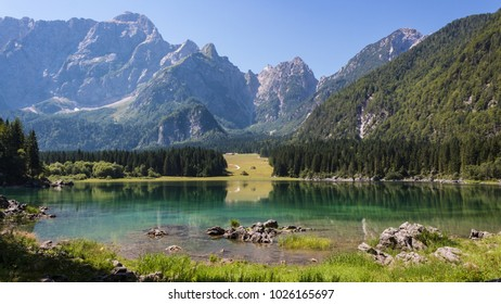 Panoramic view of Lake Fusine, trees and mountains on background. Tarvisio, Italy