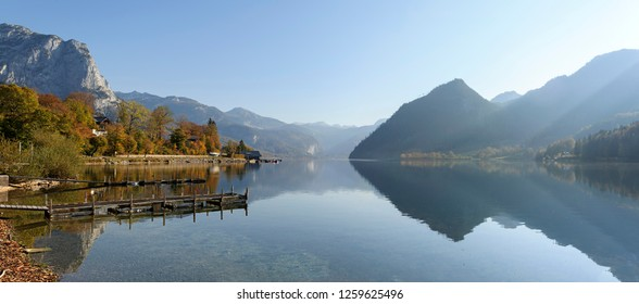 Panoramic view of the lake Grundlsee in the fall during the sunrise. View of the Alps. Village Grundlsee, region Salzkammergut, federal state of Styria, Austria, Europe.