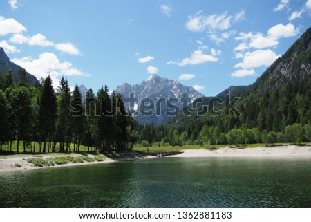 Panoramic view of lake Jasna, Kranjska Gora, Slovenia. Jasna is artificial lake popular in summer, when tourists can swim and cool in it. The lake offers scenic view of surrounding mountains.