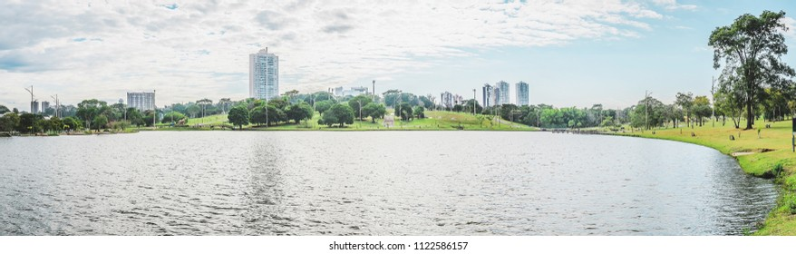 Panoramic view of the lake of a park on a beautiful sunny day. The water of the lake with some buildings on background and nature around. Photo at Campo Grande MS, Brasil.