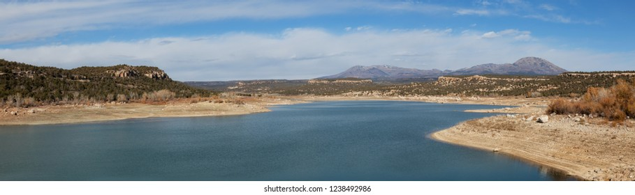 Panoramic view of a lake, Recapture Reservoir, in a desert during a vibrant sunny day. Located near Blanding, Utah, United States.