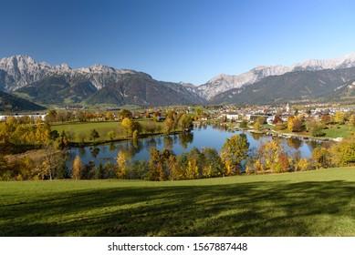 Panoramic view of Lake Ritzensee and Saalfelden on a sunny autumn day in with the mountains Steinernes Meer in the background. Saalfelden, Pinzgau, Salzburg Land, Austria. - Shutterstock ID 1567887448