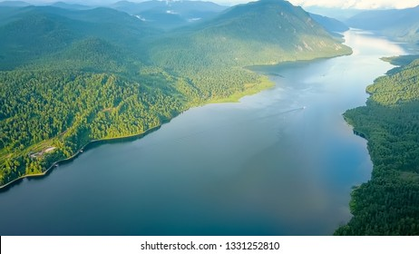 Panoramic view of Lake Teletskoye, Climbing to the clouds. Russia, Altai. Mountains covered with forests, From Drone