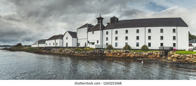 Panoramic view of Laphroaig distillery buildings. Islay island, Scotland. Grey cloudy sky before the rain. White cottages on the Scottish shoreline. Amazing autumn British landscape.