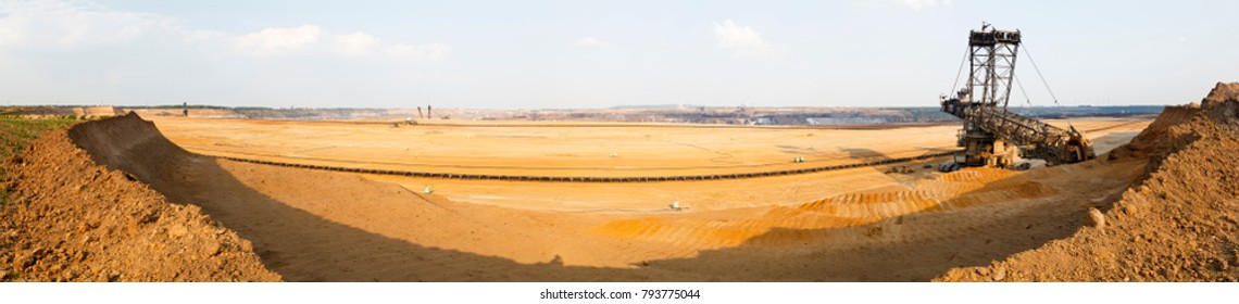 Panoramic view of a large coal pit mine with a giant bucket-wheel excavator, one of the worlds largest moving land vehicles. See the tiny looking construction vehicles and cars next to it.