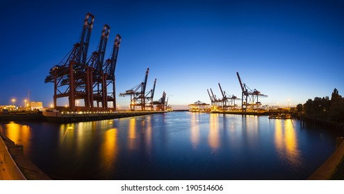 Panoramic view of a large container harbor with deep blue night sky