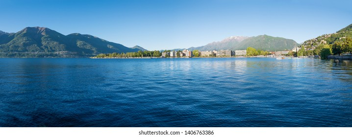 Panoramic view of a large lake between northern Italy and southern Switzerland. Lake Maggiore and the city of Locarno with the Alps in the background. In the middle the lake promenade and the port