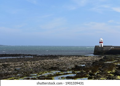 Panoramic view of the lighthouse at Castletown. The tide is low and the sea exposed the rocks covered in algae.