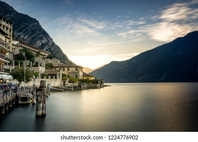Panoramic view of Limone Sul Garda, Italy during sunset with the town on the left side and the mountains in the background.