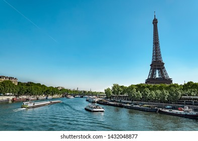 Panoramic view of living barge on the Seine in Paris with Eiffel tower and tourist and cargo boats, France
