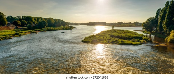 Panoramic view of the Loire River from a medieval bridge at sunset, Amboise, France. Beautiful landscape of French rural country. Horizontal banner with scenery of Loire in sun light.