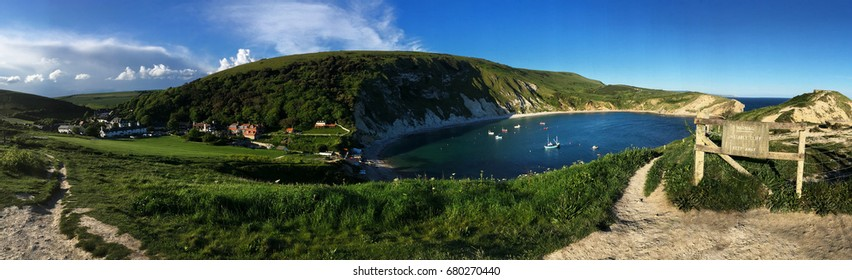 Panoramic view of Lulworth Cove and coastal walk path and green fields of West Lulworth, Dorset, England