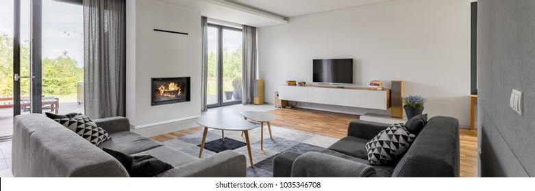 Panoramic view of luxurious living room with fireplace, tv and two couches