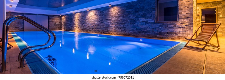 Panoramic view of luxurious swimming pool with brick wall and deck chair