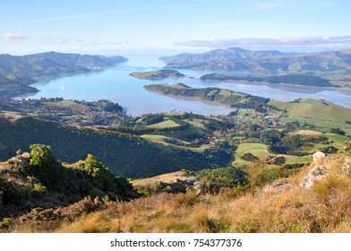 A panoramic view of Lyttelton Harbour at low tide from the top of the Christchurch Port Hills, Canterbury, New Zealand. In the background is the Port town of Lyttelton and the Pacific Ocean.