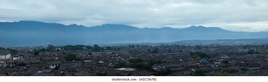A panoramic view of the main town of lijiang ancient town.Located in the old town of lijiang in yunnan, China.Old towns and mountains and clouds
