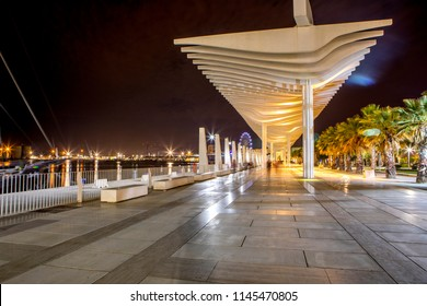 Panoramic view of Malaga port promenade, with beautiful pergola architecture, and city lights.