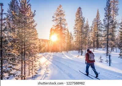 Panoramasicht auf das Skilanglauf auf einer Strecke in wunderschöner Winterlandschaft in Skandinavien mit malerischem Abendlicht bei Sonnenuntergang im Winter, Nordeuropa
