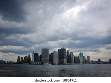 A panoramic view of Manhattan, New York City, from the Hudson river with heavy clouds.