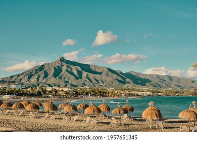 panoramic view of the Marbella mountain from the beach with umbrellas and hammocks