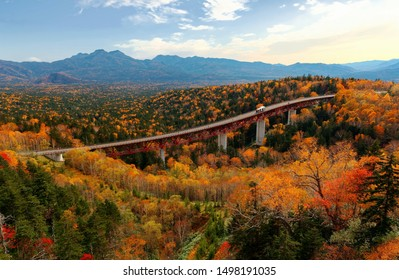 """Panoramic view of Matsumi Bridge crossing a """"sea of trees"""" in Mikuni Touge Pass, with fall colors on the mountainside & majestic mountains in background, in Daisetsuzan National Park, Hokkaido, Japan"""