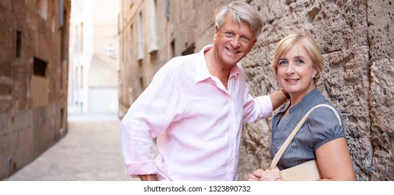 Panoramic view of mature tourist couple together visiting old city street stone architecture street, outdoors. Senior people sightseeing holiday, leisure recreation lifestyle, retirement activities.