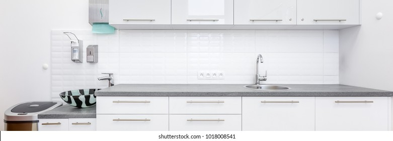 Panoramic view of a medical office with white cabinets and sink