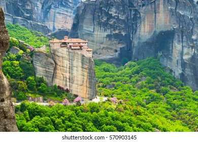 Panoramic view of Meteora monastery on the high rock and road in the mountains at spring time, Greece